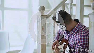 L'uomo attraente felice che si siede sulle scale con le cuffie senza fili studia il gioco della chitarra acustica a casa archivi video