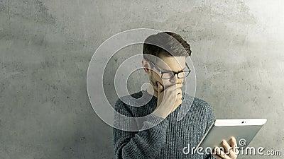L'uomo creativo dei pantaloni a vita bassa abili pensa che ipad digitale della compressa di tocco ottenga un'idea, che salta su c archivi video