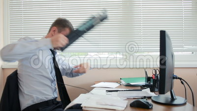 L'uomo di affari, responsabile nella rabbia fracassa la tastiera sullo scrittorio, sedentesi nell'ufficio stock footage