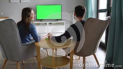 L'uomo e la donna stanno seduti su sedie, baciando e guardando la TV con uno schermo verde, cambiando canale con un telecomando archivi video