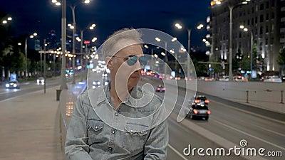L'uomo maturo posa in occhiali da sole al parapetto nell'uguagliare la città stock footage