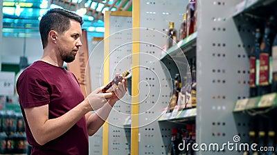L'uomo sceglie il cognac nella sala commercio al supermercato archivi video