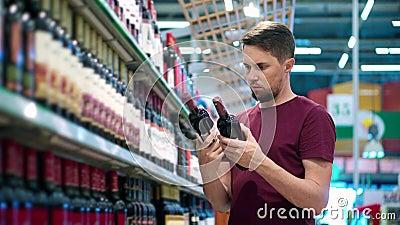 L'uomo sceglie il vino rosso nella zona del supermercato archivi video