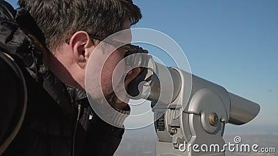 L'uomo sta guardando in telescopio turistico in montagne archivi video