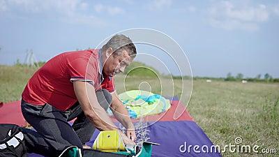 L'uomo sta imballando il paracadute, fissante le cinghie in un'aria aperta dello zaino nel giorno di estate nei campi verdi video d archivio