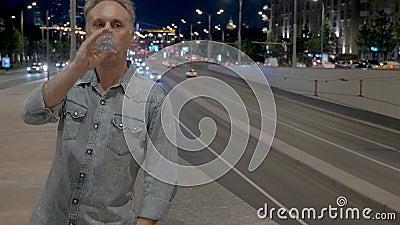 L'uomo stanco beve l'acqua che si appoggia il parapetto sopra la strada principale video d archivio