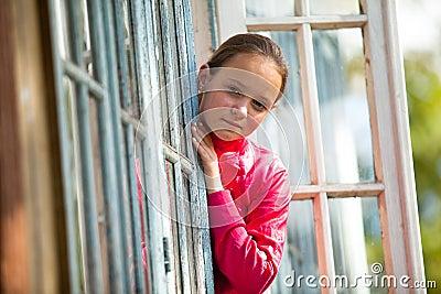 La Adolescente-muchacha mira hacia fuera la casa rural de la ventana