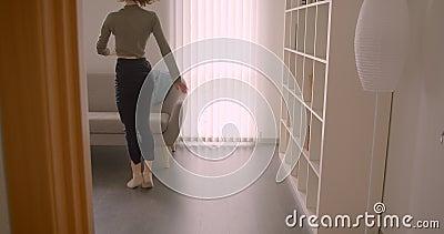 La ballerina di prima caucasica tenera che esegue il ballo contemporaneo si siede sul sofà e si rilassa alla luce ed alla stanza  video d archivio