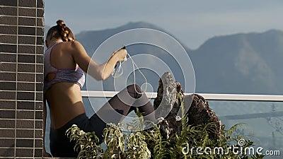La barrière de brique de terrasse de feuilles de femme se tient tout près banque de vidéos