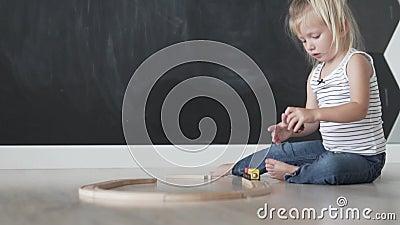La bella bambina costruisce una strada di legno per il treno nella stanza del gioco video d archivio