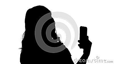 La bella donna della siluetta si pavoneggia facendo uso del suo telefono come uno specchio stock footage