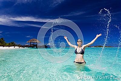La bella donna salta di grande spruzzata del mare
