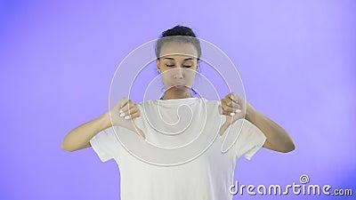 La bella ragazza in una maglietta bianca mostra il pollice giù con entrambe le mani su fondo viola archivi video