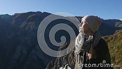 La belle femme prend un bain de soleil dans les montagnes Appréciez la lumière du soleil et le repos banque de vidéos