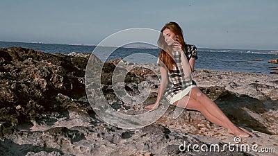 La belle femme repose l'océan côtier de pierres banque de vidéos