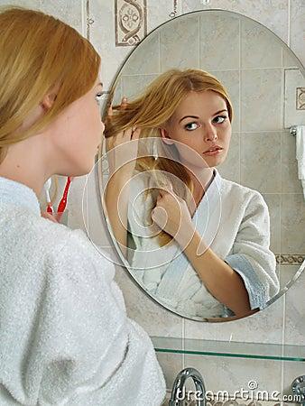 La belle fille regarde dans un miroir dans une salle de for Un gars une fille dans la salle de bain