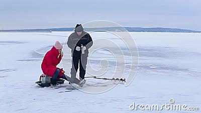 La belle pêcheuse dans les bottes rouges de veste et de feutre pêche des poissons avec la canne à pêche d'hiver d'aide banque de vidéos