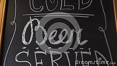 La bière froide de métier a servi ici l'insctiption par la craie blanche sur le conseil noir Invitation au bar de barre de brasse banque de vidéos