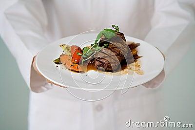La bistecca sugosa è servito dal cuoco unico