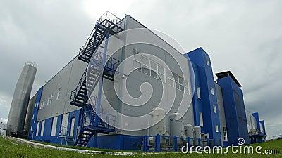La cámara se mueve al complejo de edificio grande de la fábrica almacen de video
