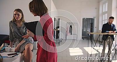 La cámara sigue a la mujer auxiliar envejecida media del negocio en el vestido rojo que entra en la oficina de moda grande del de almacen de video