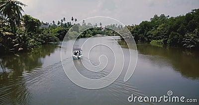 La cámara sigue a un pequeño barco blanco navegando a lo largo de un bello río tranquilo en medio de la selva tropical. almacen de metraje de vídeo