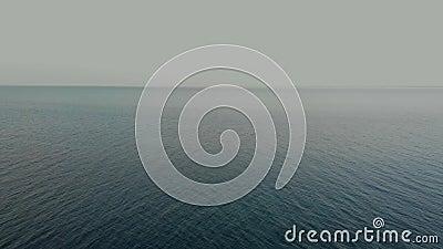 La cámara vuela sobre las borrosas olas del océano hasta el horizonte limpio Vista aérea metrajes