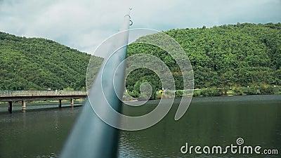 La caña de pescar se coloca en el soporte, puente está en la distancia almacen de video