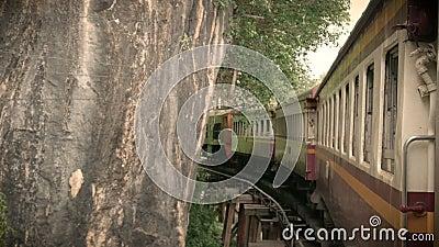 la cantidad 4K de un tren antiguo que corría en un sostenido curvó el carril que curvaba sobre un puente a través del río Kwai, f almacen de metraje de vídeo