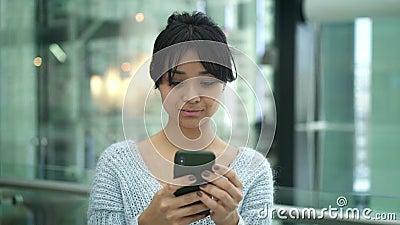 La casserole de portrait a tiré le mouvement lent de la position femelle asiatique sérieuse dactylographiant au téléphone clips vidéos