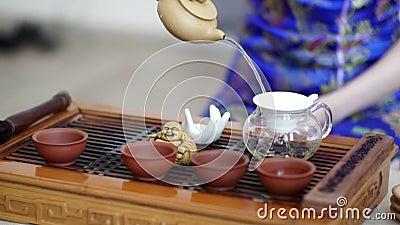 La ceremonia de té china, muchacha en un vestido azul, vierte té fragante a través de un tamiz en la caldera almacen de video