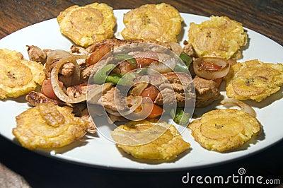 La comida asada a la parrilla del fajita del pollo con los tostones locales frió llantenes