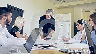 La compagnie de jeunes employés lors d'une réunion avec le chef de projet offre leurs options pour la mise en oeuvre du projet clips vidéos