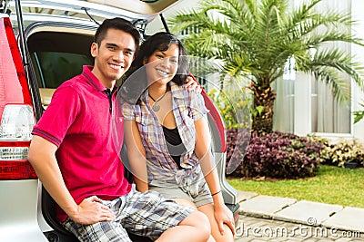 La coppia asiatica è felice nella parte anteriore l automobile