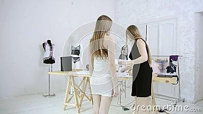 La couturière prend des mesures avec la femme pour les robes de couture dans le studio banque de vidéos