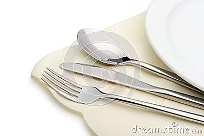 La cuchara, la fork y un cuchillo mienten en servilleta
