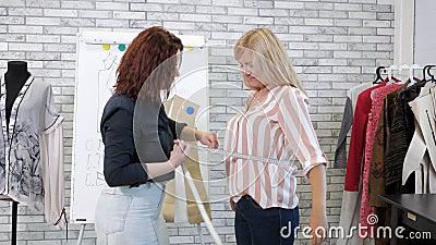 La cucitrice prende le misure con nastro adesivo del cliente della donna nell'adattamento dell'officina archivi video