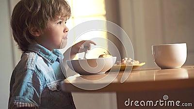 La cuill?re heureuse de b?b? gar?on se mange Peu gar?on s'asseyant ? la table et mangeant le casse-cro?te de lait B?b? mangeant d banque de vidéos