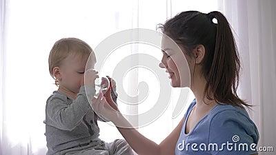 La cura materna, ragazzo di risata felice del bambino che beve l'acqua minerale pura da vetro dalla madre sorridente passa e si r video d archivio