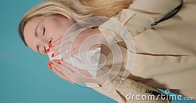 La dama de pelo largo estornuda en la pantalla vertical de pañuelo de papel blanco almacen de metraje de vídeo