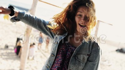 La danse heureuse de jeune fille à l'hamac sur la plage sourient in camera Jour ensoleillé insousiant clips vidéos