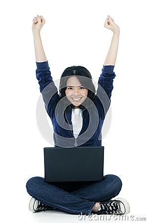 La donna allegra con il computer portatile e le braccia si è alzata