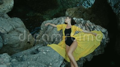 La donna attraente si trova su roccia dalla riva di mare nel giorno di estate archivi video