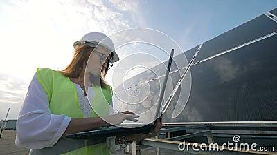 La donna attraente sta facendo funzionare il suo computer portatile mentre era vicino ad una costruzione solare stock footage