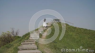 La donna dell'eleganza alza le scale su hiil verde video d archivio
