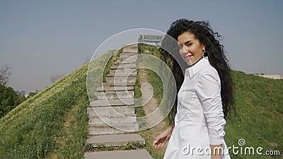 La donna dell'eleganza in vestito bianco lungo sta alzando le scale di thee sulla collina video d archivio