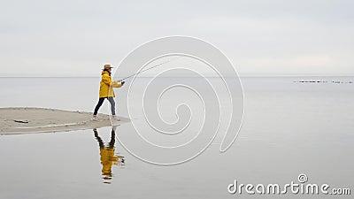 La donna femminile del pescatore in impermeabile giallo getta le attrezzature di pesca con la barretta di filatura al rallentator archivi video