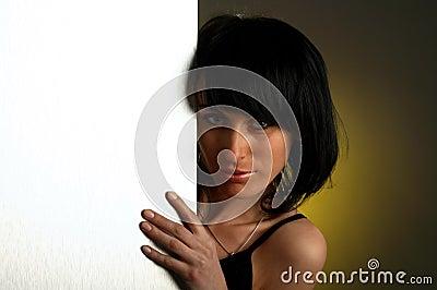 La donna sta osservando fuori-della scheda vuota bianca