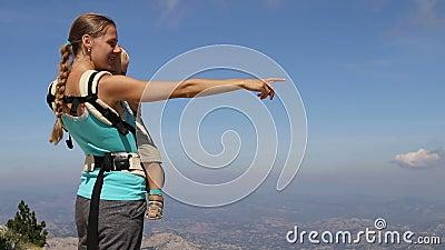 La donna tiene il figlio in mani e punti sulle montagne, vista laterale video d archivio
