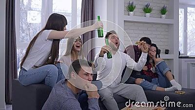 La emoción, fans que miran el partido de fútbol en la TV con el entusiasmo y entonces disfruta en la victoria que se sienta en el almacen de video